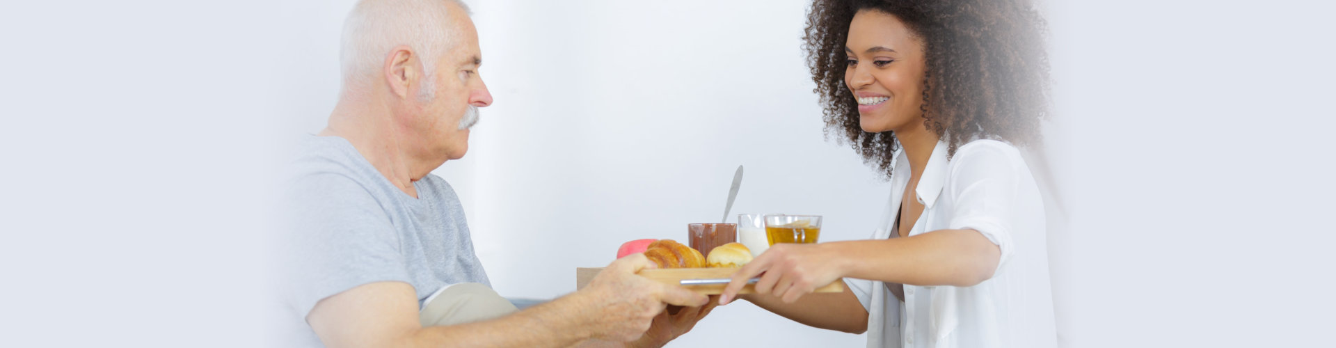 Care worker giving lunch to senior