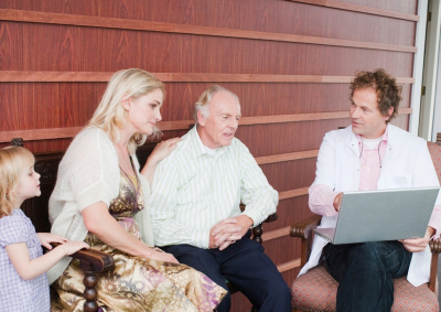 An elderly man and his family talking to a medical consultant